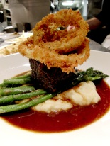 "Braised boneless beef short ribs with Spring-dug parsnip whipped potatoes, broccolini and ""bistro"" style onion rings"
