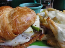 Granny Melt: A grilled croissant with melted Swiss & cheddar, green apple slices & red onions sautéed in brown sugar