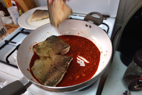 Adding the fish back in to the paprika base.