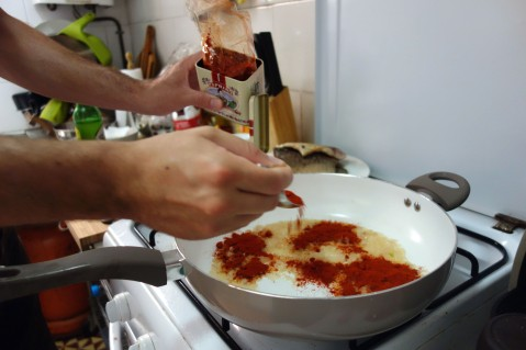 Adding paprika to the minced and sauteed onions to make the paprikás base. Important to turn the heat off when doing so, as paprika burns quite easily.