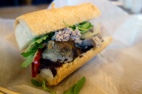 The Jeneric with hunks of smoked pork, a salad of chopped olives, caramelized onoions, roasted red peppers, chive aioli on a baguette