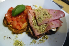 Bruschetta with mortadella and pistachios, tomato and basil